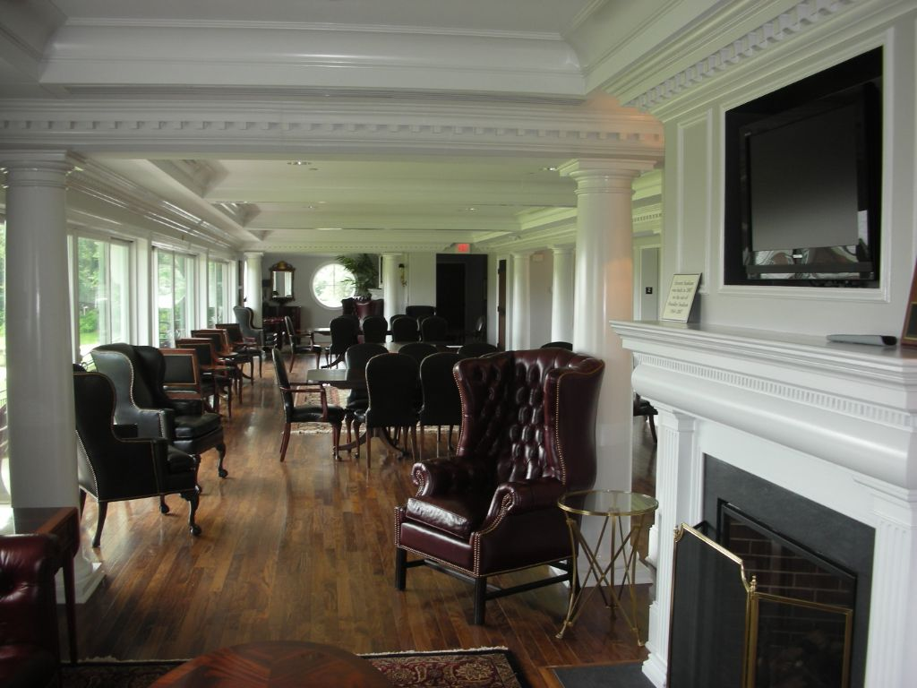 interior view of the the football stadium luxury lounge with large windows, leather chairs, and fireplace